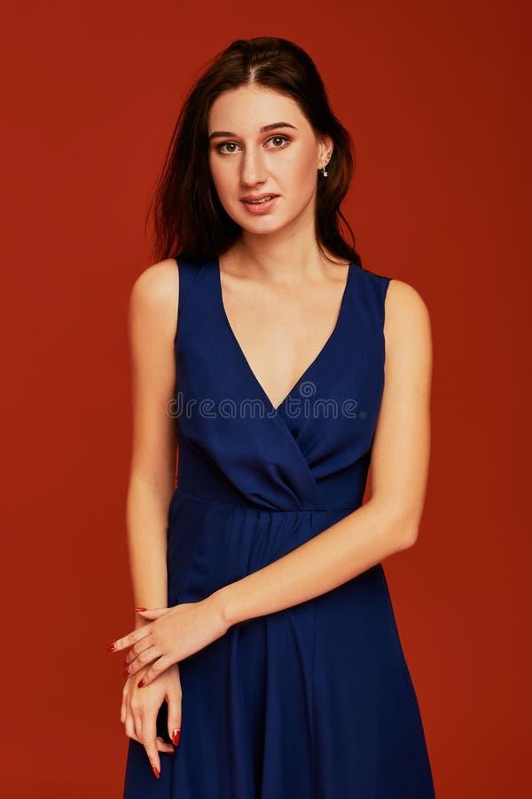 La belle jeune femme de brune dans la robe de cocktail bleue élégante avec decollete profond pose pour la caméra photo stock