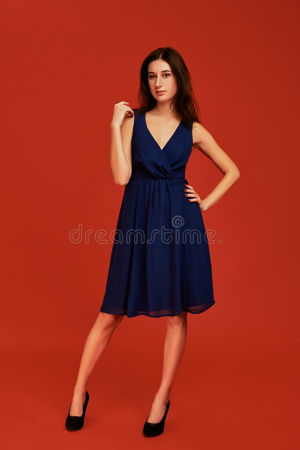 La belle jeune femme de brune dans la robe de cocktail bleue élégante et des talons hauts noirs pose pour la caméra photo stock