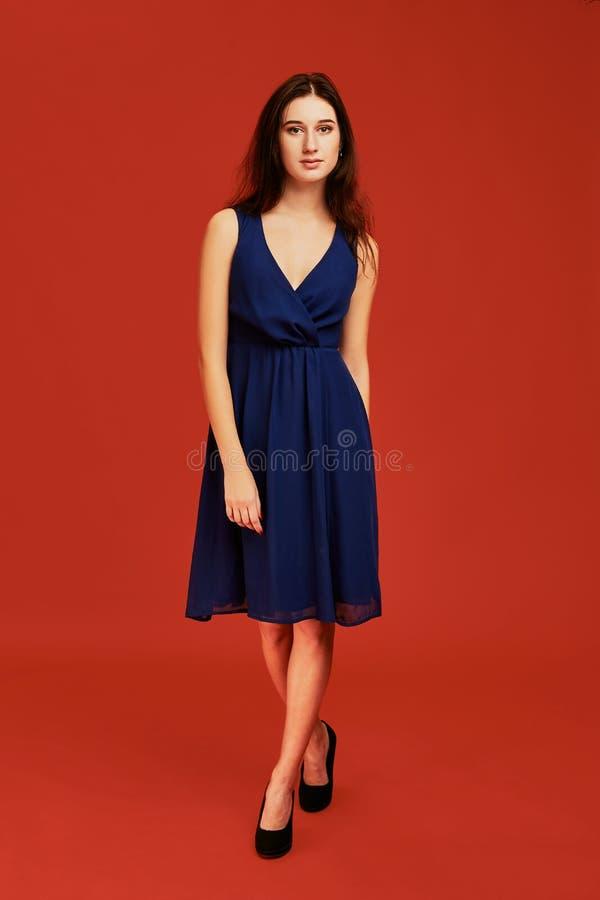 La belle jeune femme de brune dans la robe de cocktail bleue élégante et des talons hauts noirs pose pour la caméra photos stock