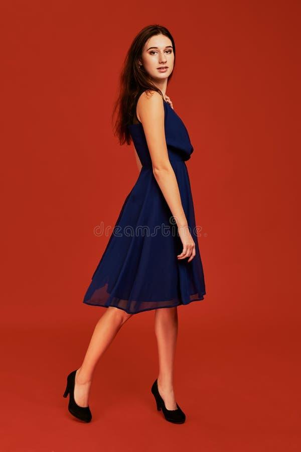 La belle jeune femme de brune dans la robe de cocktail bleue élégante et des talons hauts noirs pose pour la caméra photo libre de droits