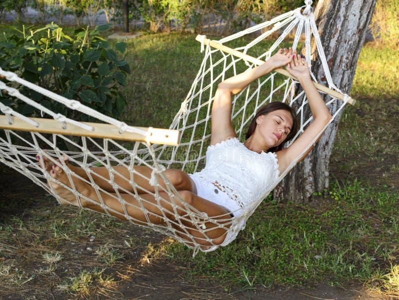 La belle jeune femme de brune se situe dans un hamac appréciant le repos a photographie stock
