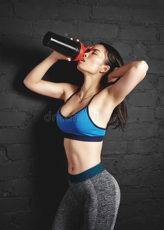 La belle jeune femme de forme physique de mode folâtre des vêtements Dispositif trembleur de nutrition de sport de prise de fille photo libre de droits