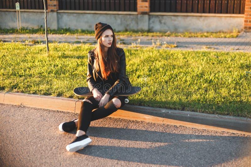La belle jeune femme de mode s'assied sur le conseil avec une planche à roulettes images libres de droits
