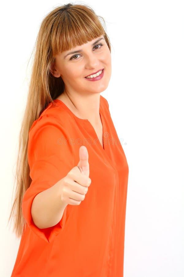 La belle jeune femme de sourire heureuse montrant des pouces lèvent le geste, I photographie stock