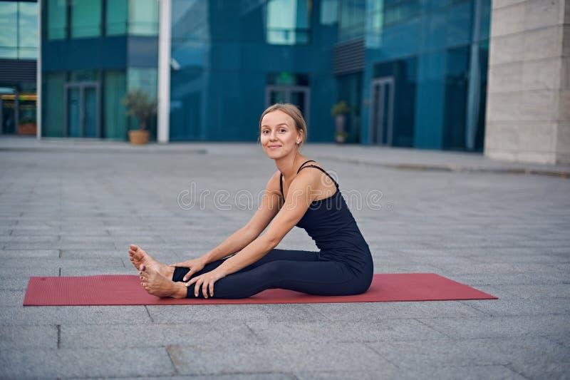 La belle jeune femme dispose à pratiquer le yoga dehors dans la perspective d'une ville moderne photographie stock