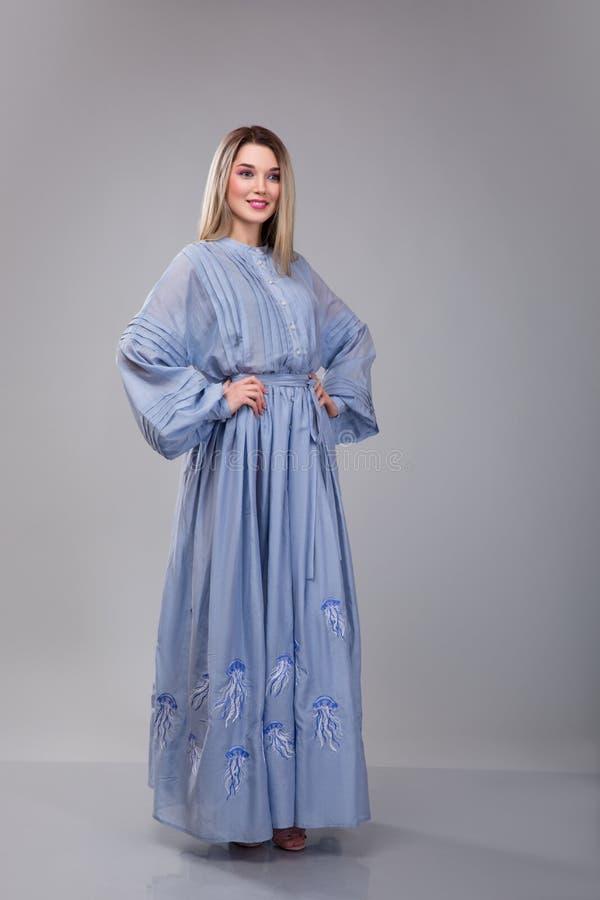 La belle jeune femme dresseed dans la robe brodée long par bleu sur le fond gris de studio photographie stock libre de droits