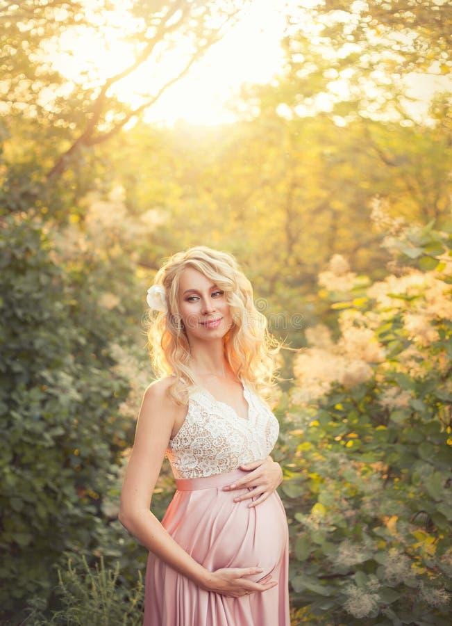 La belle jeune femme enceinte aimable est sourire, portant une robe élégante rose avec le dessus blanc de dentelle dans les rayon image stock