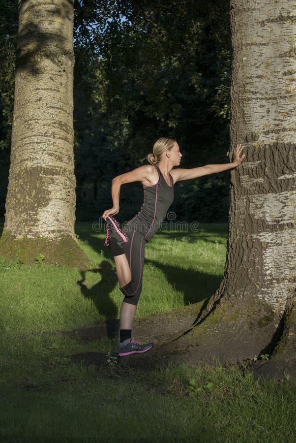 La belle jeune femme fait des exercices dehors en parc images libres de droits
