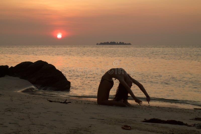La belle jeune femme fait des exercices gymnastiques sur la plage photographie stock