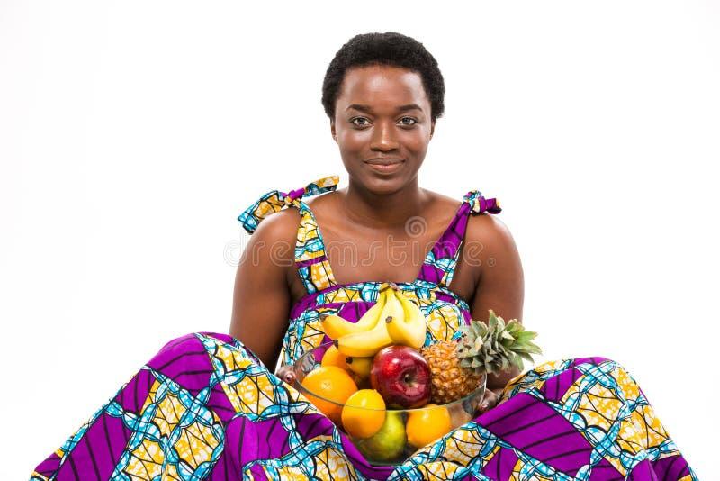 La belle jeune femme gaie d'afro-américain s'asseyant et se tenant porte des fruits photographie stock