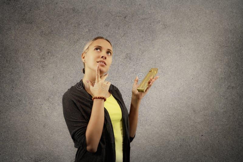 La belle jeune femme gaie en tissus occasionnels se demandent ce qui est boîte actuelle d'or intérieure dans des ses mains images libres de droits