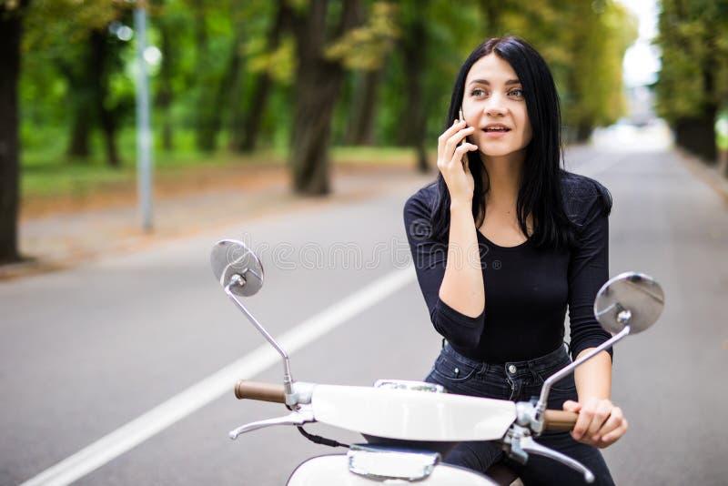 La belle jeune femme a habillé la séance occasionnelle sur le scooter et parler au téléphone photo libre de droits