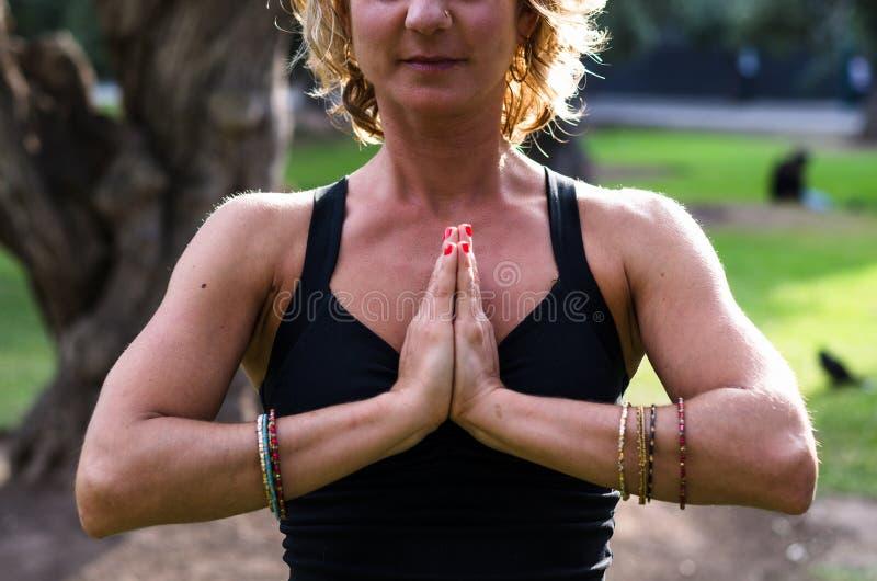 La belle jeune femme médite dans l'asana Padmasana de yoga - la pose de Lotus sur la plate-forme en bois en parc d'automne photographie stock