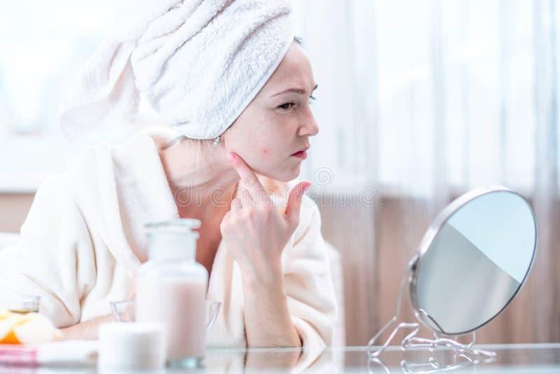 La belle jeune femme malheureuse avec une serviette sur sa tête détecte l'acné sur son visage Hygiène et entretenir la peau image stock