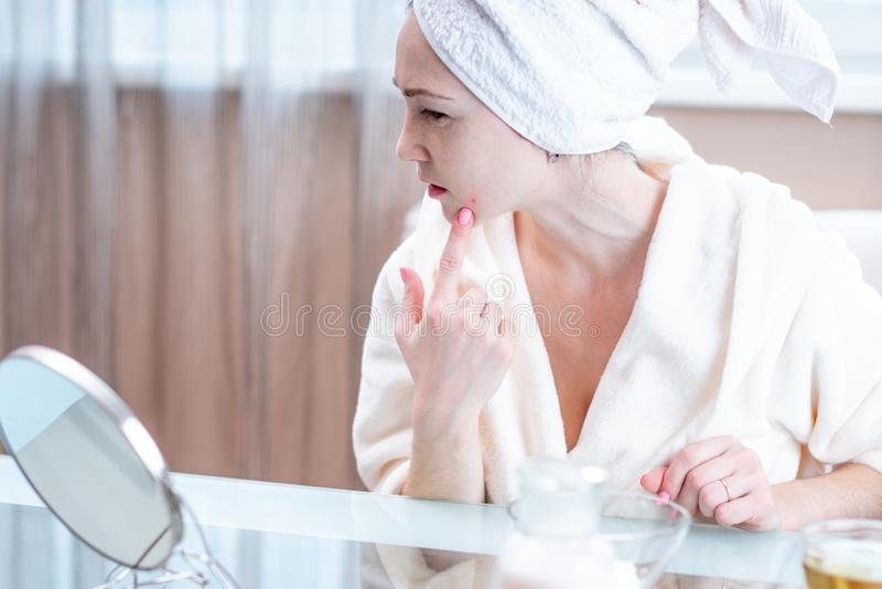 La belle jeune femme malheureuse avec une serviette sur sa tête détecte l'acné sur son visage Hygiène et entretenir la peau images libres de droits