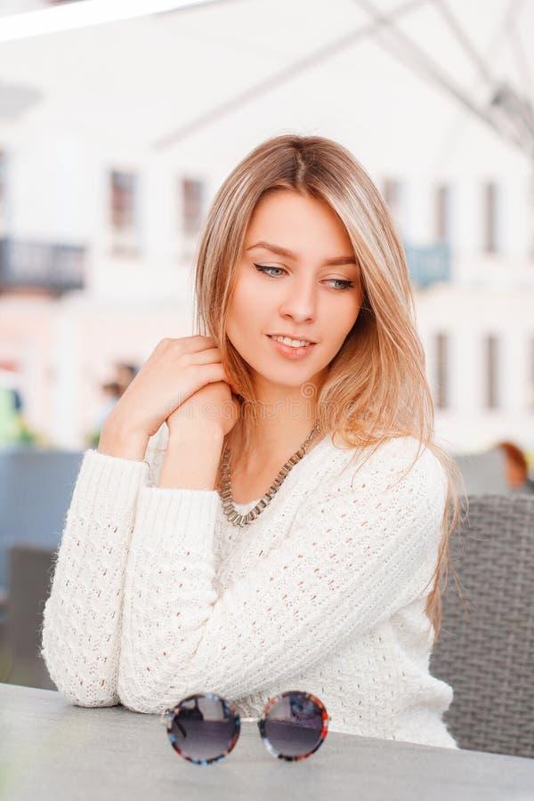 La belle jeune femme merveilleuse dans un chandail tricoté par cru tricoté avec des yeux bleus est se reposante et rêvante en été images stock