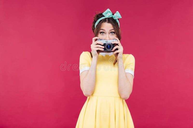 La belle jeune femme mignonne a couvert son visage de vieil appareil-photo images stock