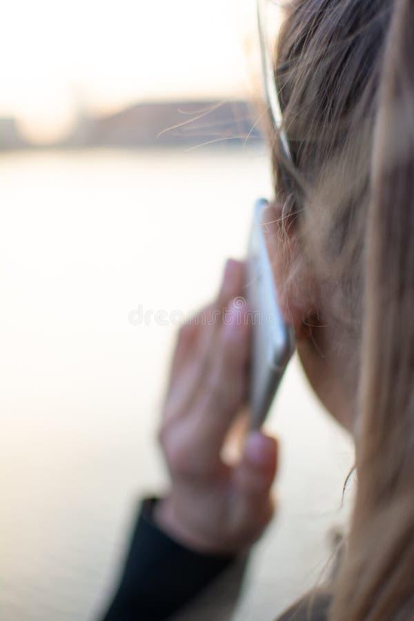 La belle jeune femme parle par le téléphone avec la vue sur la ville Profondeur de zone Foyer s?lectif photographie stock