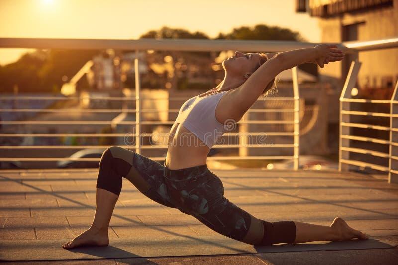 La belle jeune femme pratique l'asana Virabhadrasana 1 de yoga - la pose 1 de guerrier dans la terrasse au coucher du soleil photographie stock