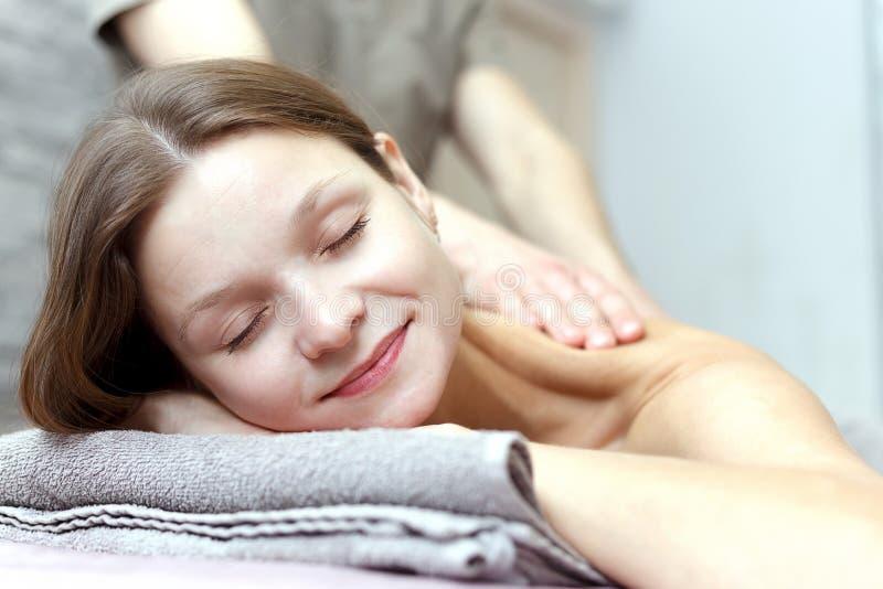 La belle jeune femme re?oit un massage ? un salon de massage images stock