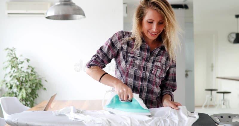 La belle jeune femme repasse des vêtements à la maison photos libres de droits