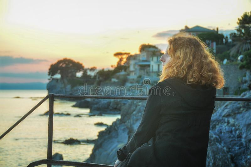 La belle jeune femme rousse, au bord de la mer dans le village de pêche en Ligurie, l'Italie apprécie le coucher du soleil images libres de droits