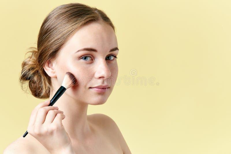 La belle jeune femme rousse avec des taches de rousseur contournant ses pommettes utilisant composent la brosse Verticale de beau image libre de droits