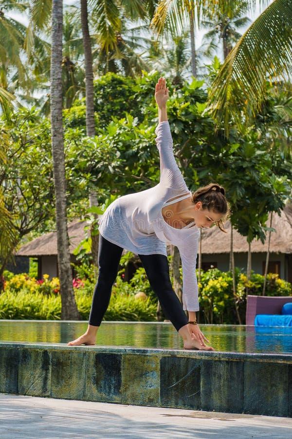 La belle jeune femme s'étire dans la pose de yoga au bord de la piscine dans la station de vacances en Indonésie photo stock