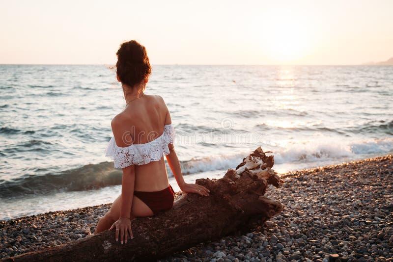 La belle jeune femme s'asseyant sur la plage au coucher du soleil et médite images libres de droits