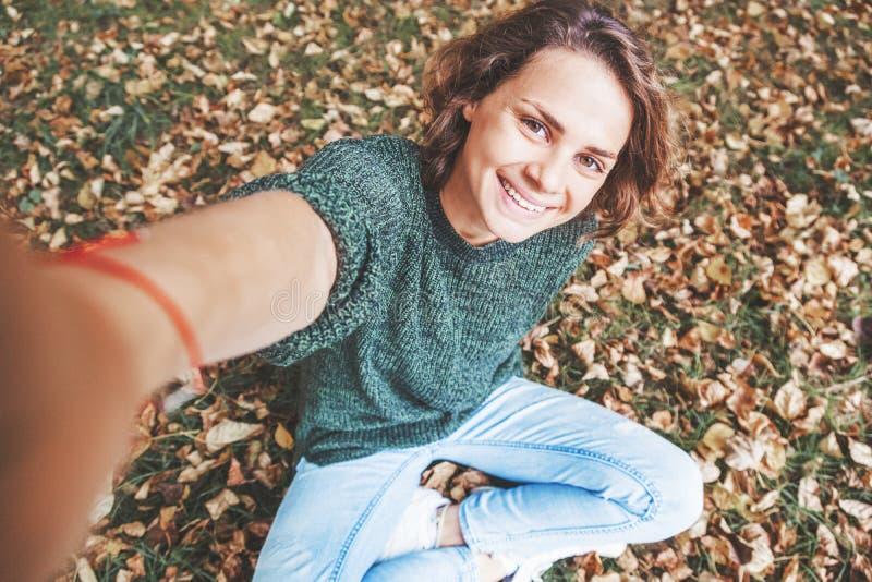 La belle jeune femme s'asseyent en parc sur le feuillage d'automne et font photos stock