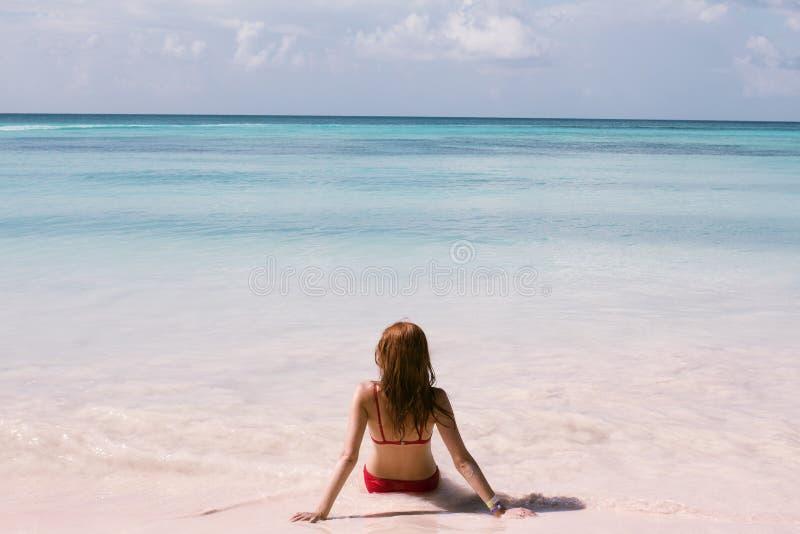 La belle jeune femme s'assied sur le sable, plage tropicale photo stock