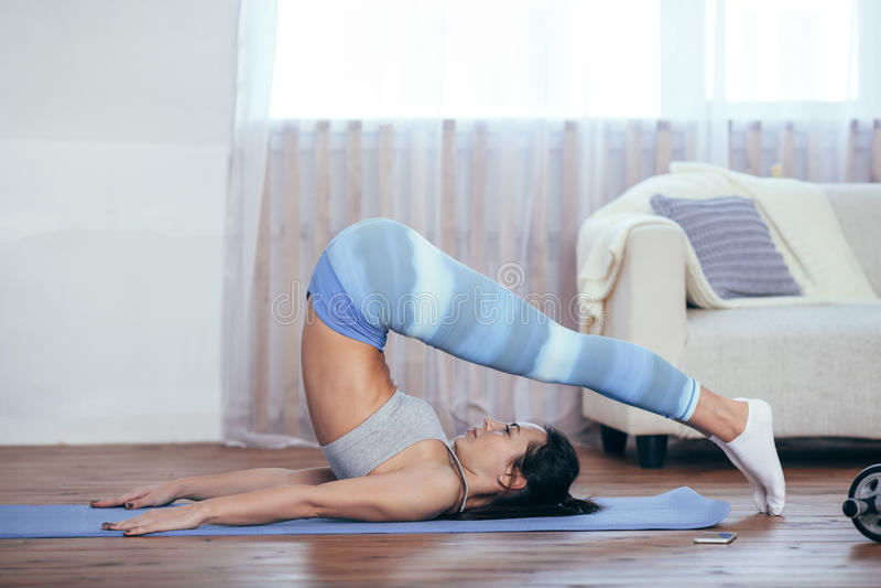 La belle jeune femme s'est habillée dans les vêtements de sport faisant le yoga à l'intérieur photo stock