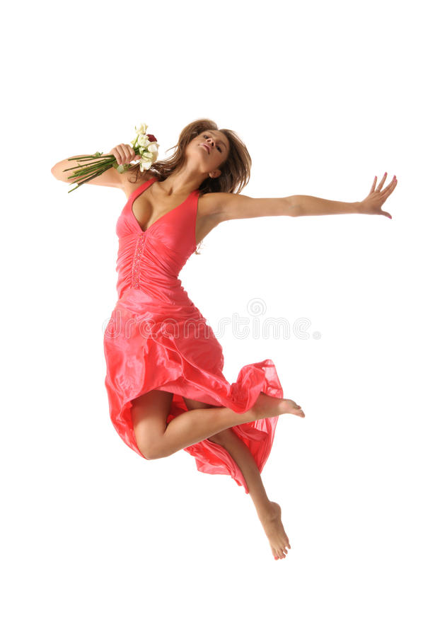 La belle jeune femme saute avec la fleur photo stock