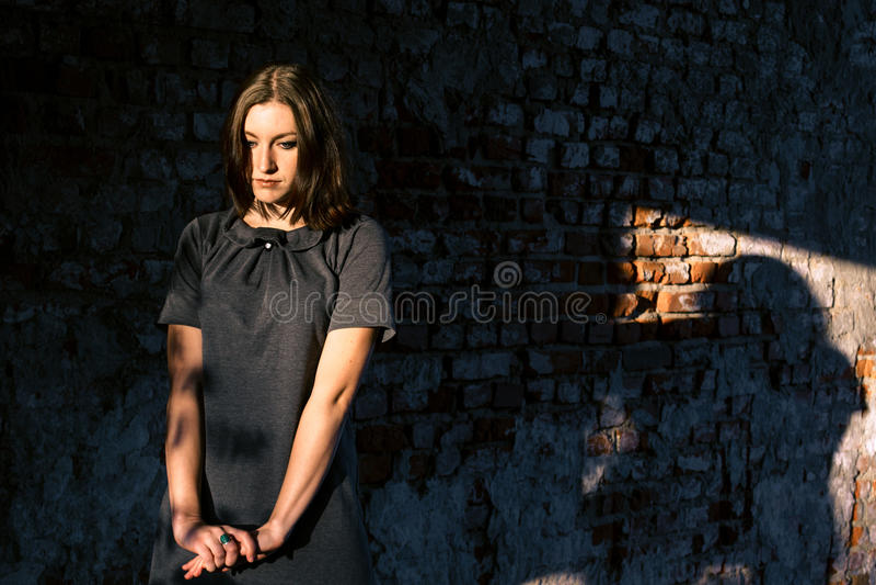 La belle jeune femme se tient près du vieux mur de briques image stock