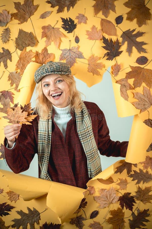 La belle jeune femme se trouve sur le fond en bois Étonnez la femme jouant avec des feuilles et regardant l'appareil-photo Jeunes photographie stock