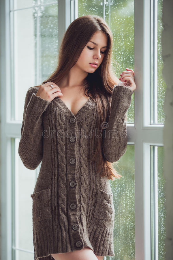 La belle jeune femme seul se tenant près de la fenêtre avec la pluie se laisse tomber Fille sexy et triste Concept de solitude photographie stock