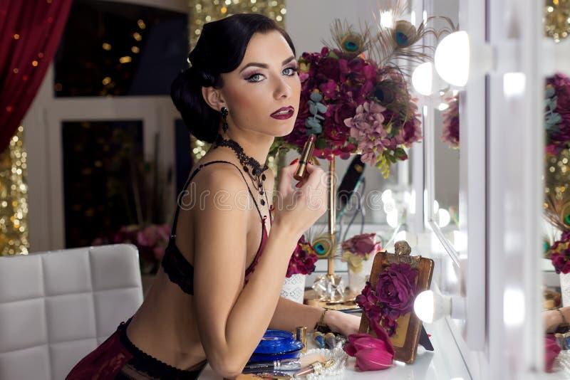 La belle jeune femme sexy applique le rouge à lèvres avant un miroir dans le vestiaire dans les sous-vêtements de dentelle dans u photographie stock