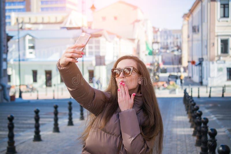 La belle jeune femme souffle un baiser d'air tout en posant pour un selfie images stock