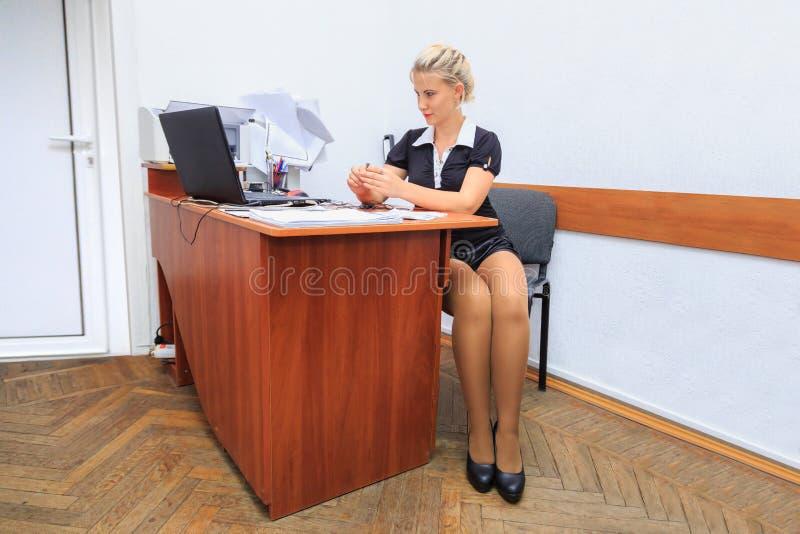 La belle jeune femme travaille dans le bureau photo stock