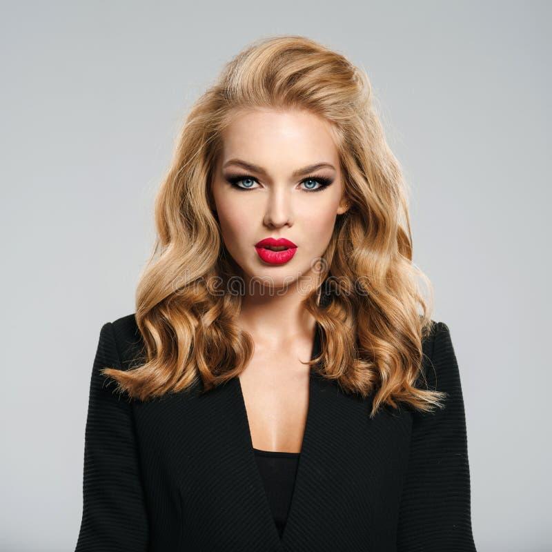 La belle jeune fille avec de longs cheveux utilise la veste noire photo libre de droits