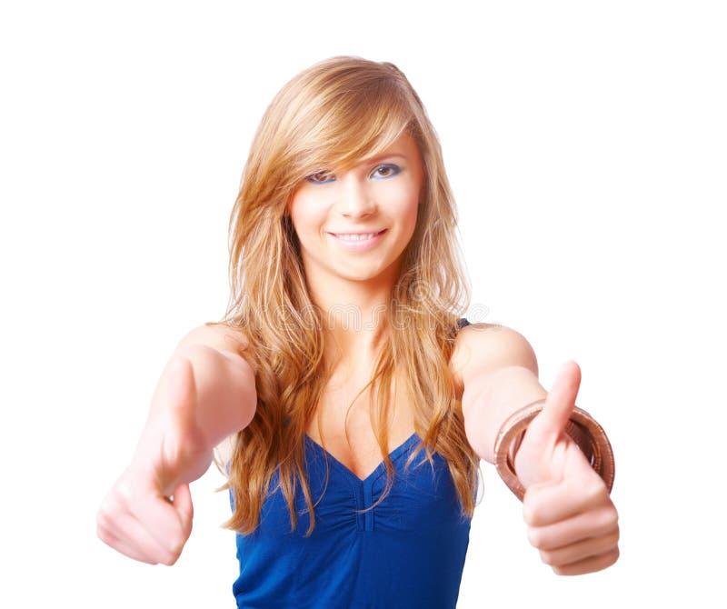 La belle jeune fille avec des pouces lèvent le signe photographie stock libre de droits