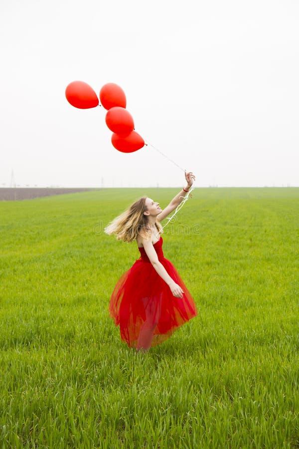 La belle jeune fille avec les cheveux blonds dans la robe rouge tient des ballons et les mouvements giratoires en été vert metten photographie stock