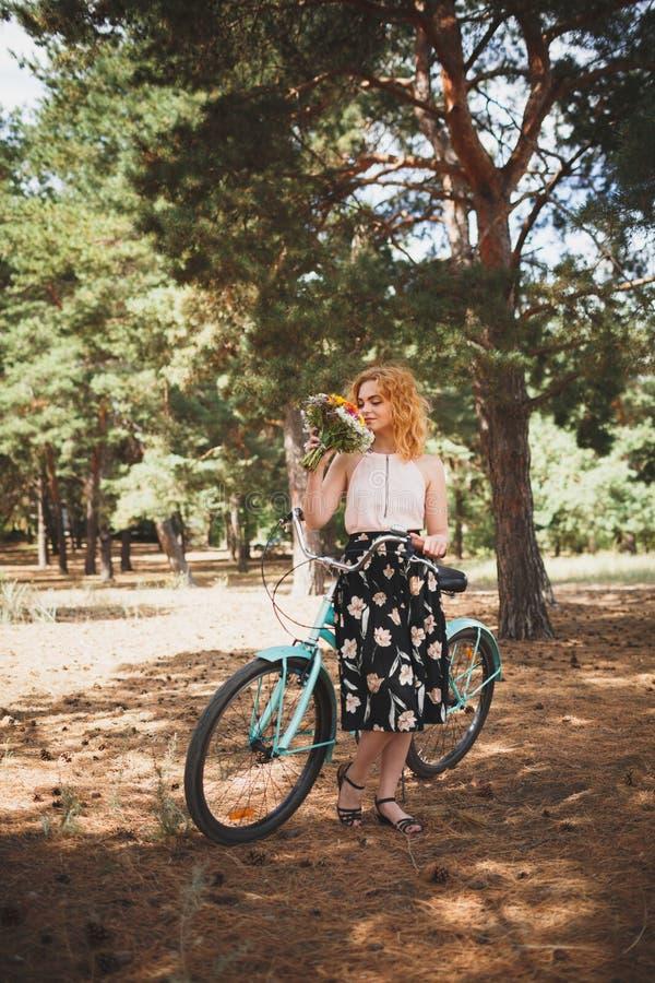 La belle jeune fille avec son croiseur de vélo et les fleurs l'automne mettent en place La meilleure heure de marcher avec une bi image libre de droits