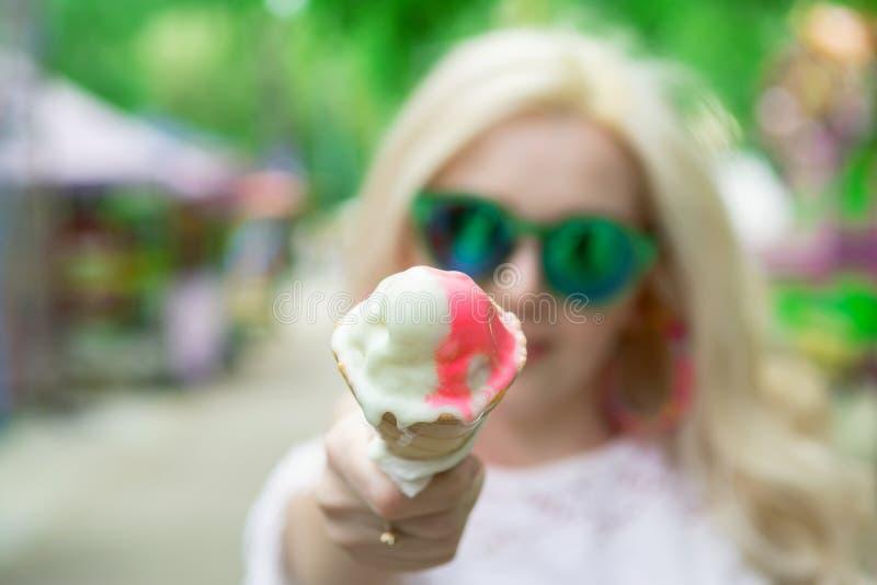 La belle, jeune fille blonde avec la crème glacée dans des ses mains, lèche la crème glacée sur le fond d'un parc vert Cr?me glac photos libres de droits