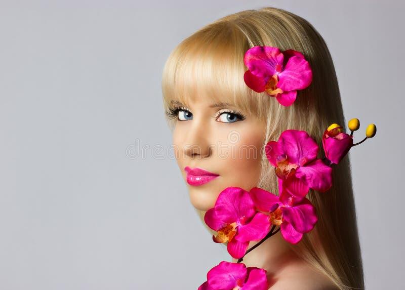 La belle jeune fille blonde avec l'orchidée fleurit sur le backgrou gris photos libres de droits
