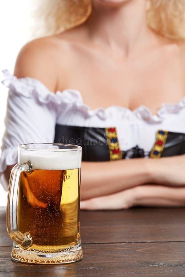 La belle jeune fille blonde dans le costume traditionnel boit hors de la chope en grès de bière oktoberfest photo stock