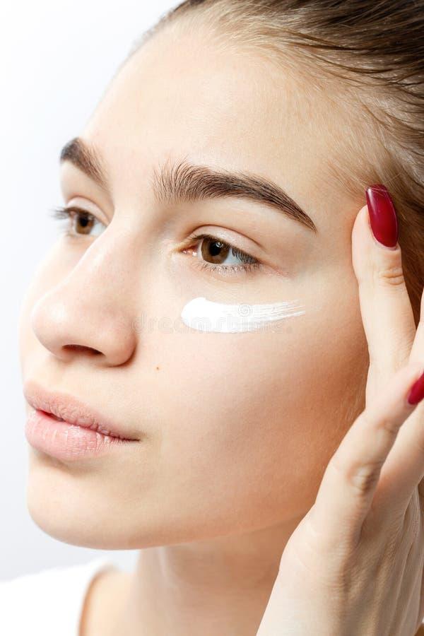 La belle jeune fille châtain sans maquillage met une crème sur son visage sur le fond blanc images stock