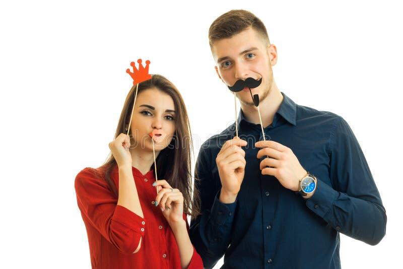 La belle jeune fille dans les supports rouges d'un chemisier avec un type et eux tiennent la moustache, la couronne et les éponge photo stock