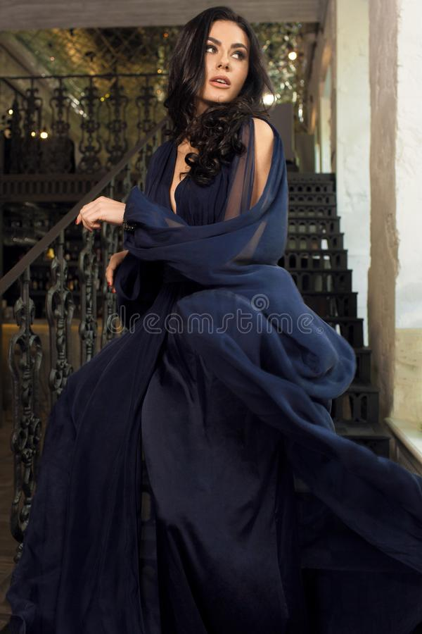 La belle jeune fille dans la robe bleue, fonctionnant regarde en arrière sur le St photo stock