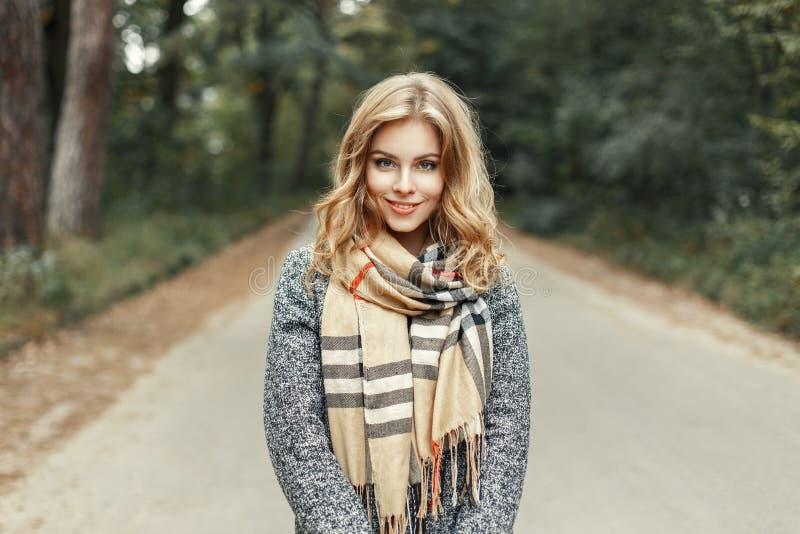 La belle jeune fille dans une écharpe de vintage marche en parc d'automne photos stock
